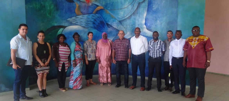 """Ante el mural de la obra """"Cuando la muerte sedujo al Maestro"""", la embajadora, el Ministro de Juventud y Deportes de Gambia, y la comitiva que los acompañó, junto a los directivos de la UCI que los recibieron"""