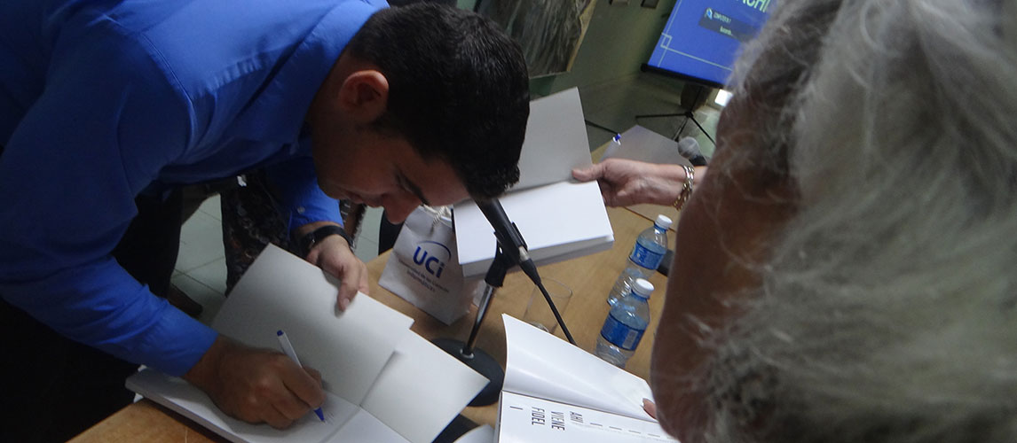 Wilmer Rodríguez Fernández, uno de los autores de Ahí viene Fidel, firma el libro adquirido por estudiantes y trabajadores de la UCI