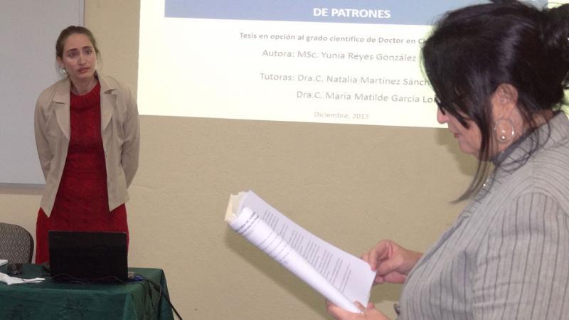 La MSc. Yunia Reyes, vicedecana de la Facultad 2, atenta a la lectura de su caracterización, previa a comenzar la defensa de su tesis doctoral.
