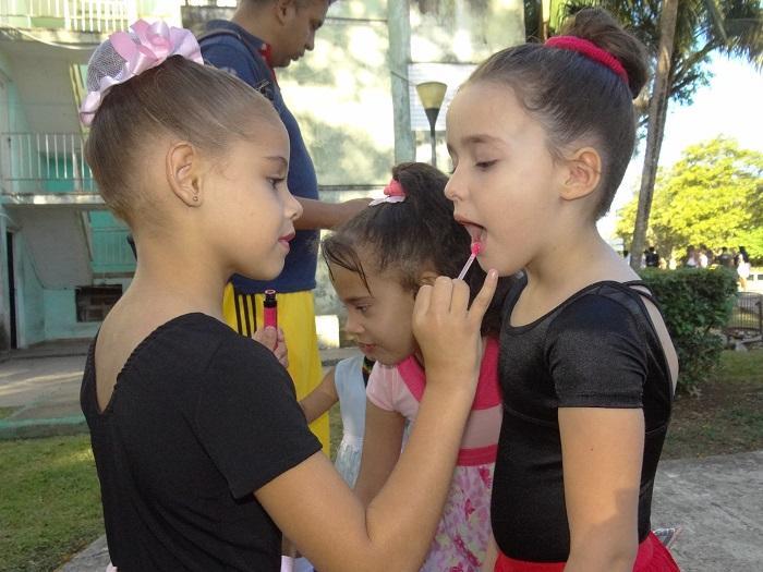 Niños de PequeCiudad maquillándose para la actividad.