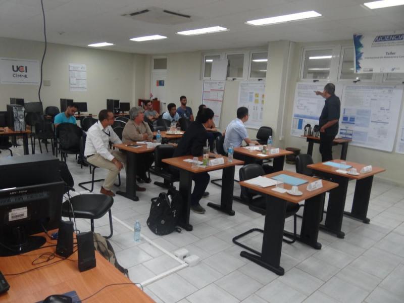 El profesor auxiliar Ing. Edisel Navas Conyedo, explica a los visitantes los pósteres de proyectos ejecutados por el Centro de Matemática Computacional de la UCI.