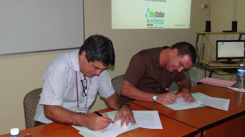 El director de la Dirección de Transferencia de Tecnología MSc. Rafael Torralbas Ezpeleta y el Lic. Eulogio Pimentel Vázquez, director del Centro de Ingeniería Genética y Biotecnología realizan el intercambio de firmas para nuevos convenios de trabajo UCI-BioCubaFarma.