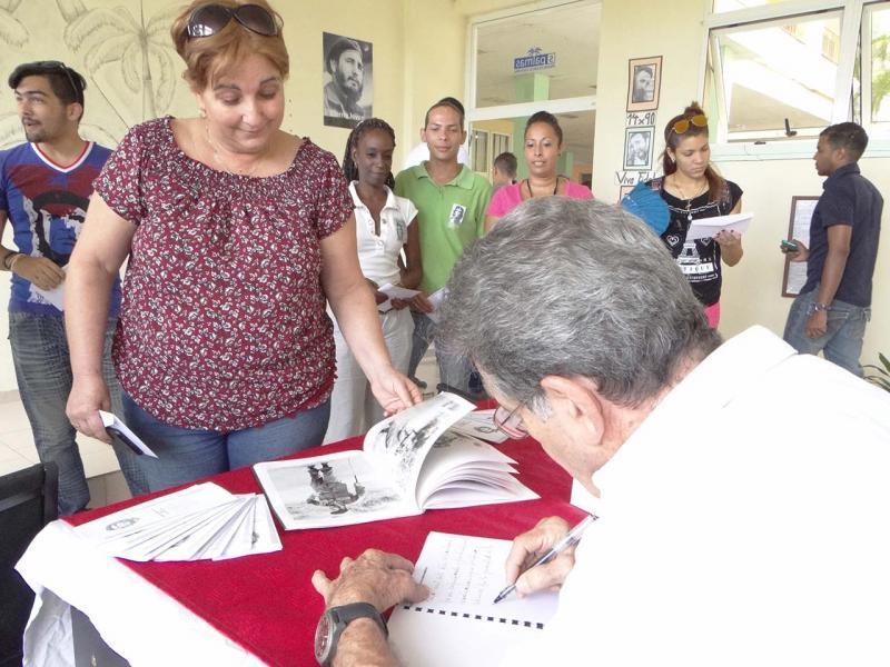 El Comandante Oscar Fernández Mell firma el libro de visitantes.